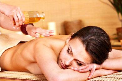 En kvinne får massasjeolje på ryggen